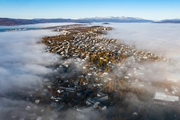 Ripresa aerea mozzafiato del paesaggio urbano circondato da alberi verdi sotto un cielo nuvoloso panoramico