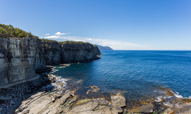 Breathtaking high angle shot of the cliffs near the pure water of eaglehawk neck in australia