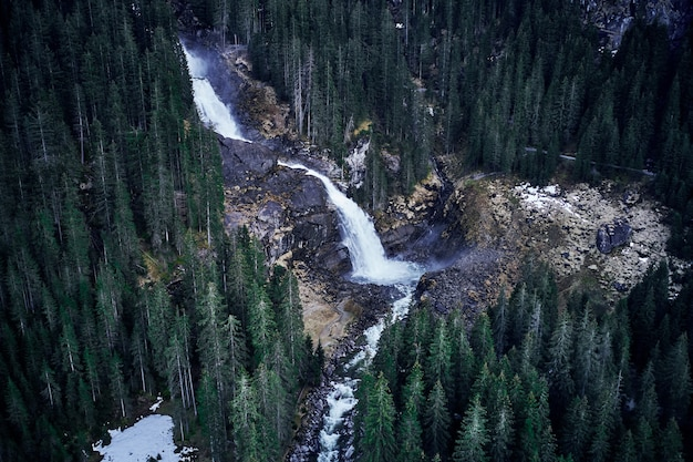 Breathtaking high angle shot of a waterfall on a rock surrounded by a forest of tall spruces