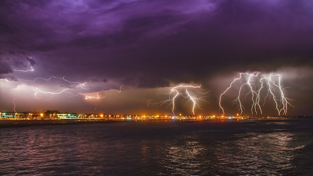 Breathtaking intense lightning storm over the ocean in the city of esposende, portugal