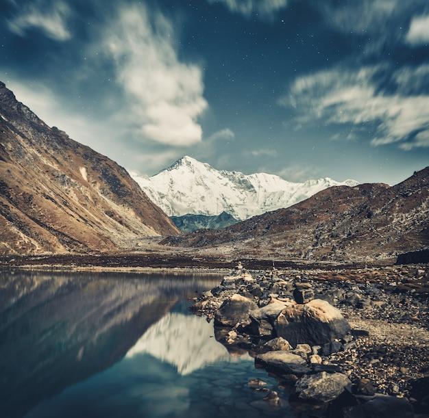 수정처럼 맑은 고쿄 호수와 회색 푸른 색조의 눈 덮인 히말라야의 숨막히는 장면. 네팔 북동부에 있는 사가르마타 국립공원의 보호 구역.