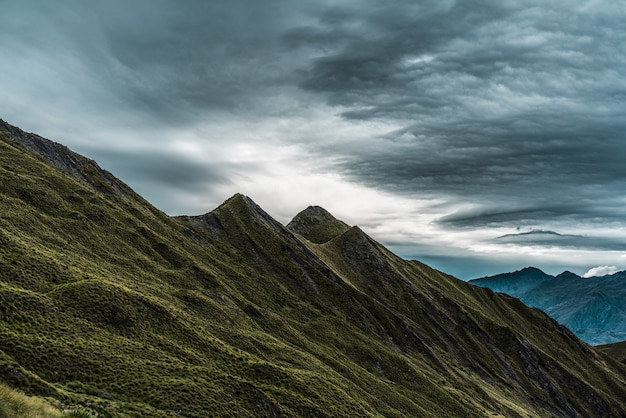 Breathtaking scenery of the historic roys peak touching the gloomy sky in new zealand