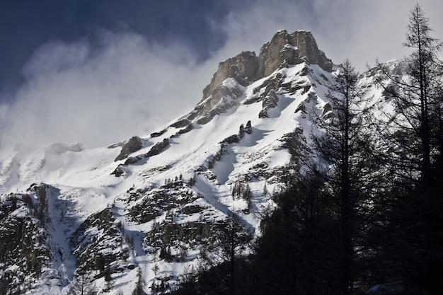 Захватывающие пейзажи заснеженных гор под живописным облачным небом