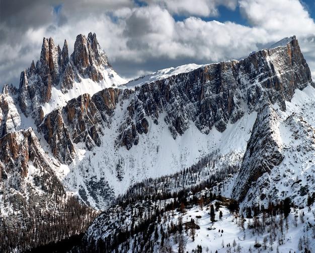 冬のイタリアアルプスのドロミテンで曇り空の下で雪に覆われた岩の息をのむような風景