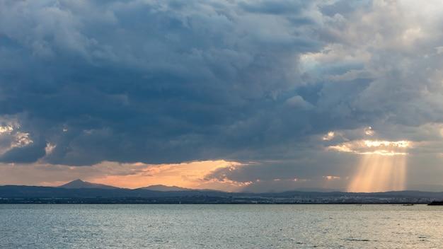 穏やかな海に浮かぶ雲の切れ間から輝く夕日の息を呑むような風景