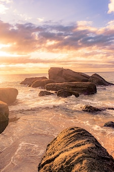 Breathtaking scenery of a rocky beach on a beautiful sunset