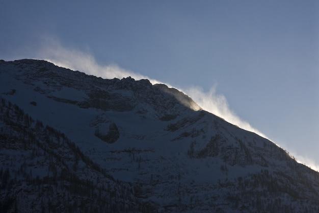 Paesaggi mozzafiato delle montagne innevate sotto un suggestivo cielo nuvoloso