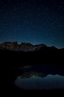 Breathtaking scenery of the starry sky and rocky cliffs reflecting on the lake at night time