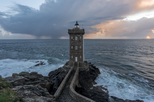 Breathtaking shot of a beautiful lighthouse standing at the seashore under the cloudy sky