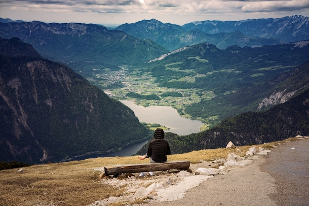 Breathtaking shot of a female sitting in the hoher dachstein's area
