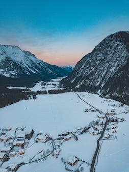 Scatto mozzafiato di una catena montuosa con una città sottostante in inverno durante il tramonto