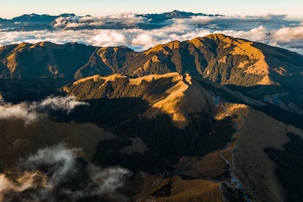 Scatto mozzafiato del paesaggio montuoso sopra le nuvole panoramiche