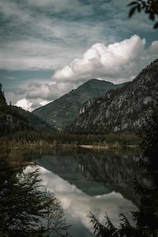 Scatto mozzafiato delle montagne con un lago in primo piano sotto un cielo nuvoloso