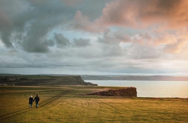 日没時に崖の上で手をつないで歩いているカップルの息を呑むようなショット