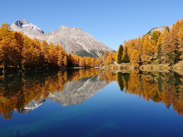 Захватывающий снимок отражающего озера на поверхности горного пейзажа.