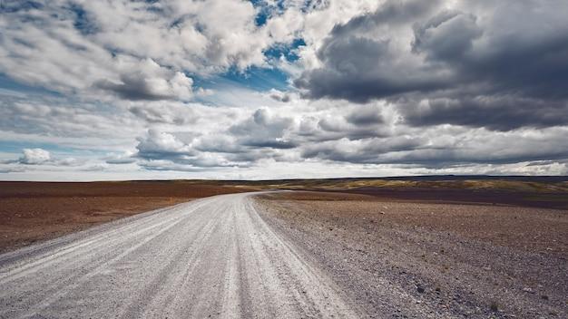 曇り空の下の美しい畑を伸びる人里離れた道の息を呑むようなショット