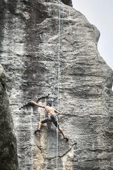 프랑스 champfromier의 높은 바위를 등반하는 젊은 남성의 숨막히는 사진