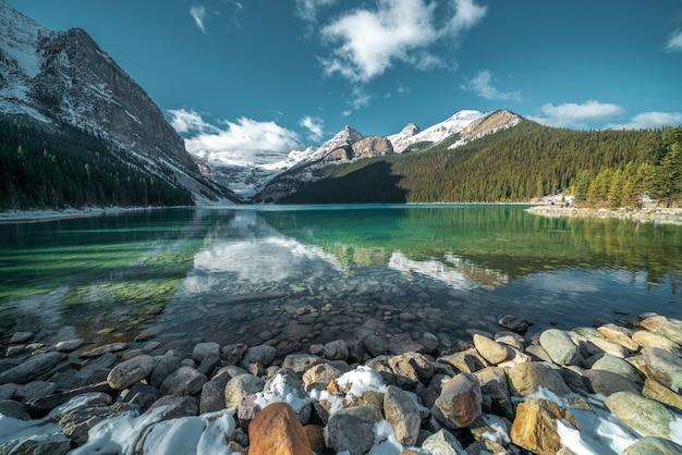 백그라운드에서 호수와 언덕의 청록색 물 아래 아름다운 돌의 숨막히는 샷