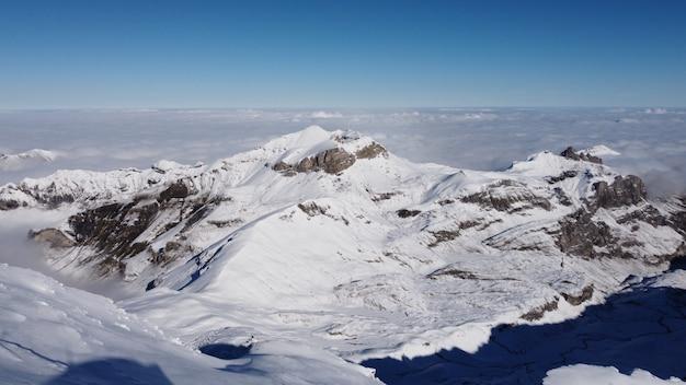 雲に覆われた雪山の頂上からの息をのむようなショット