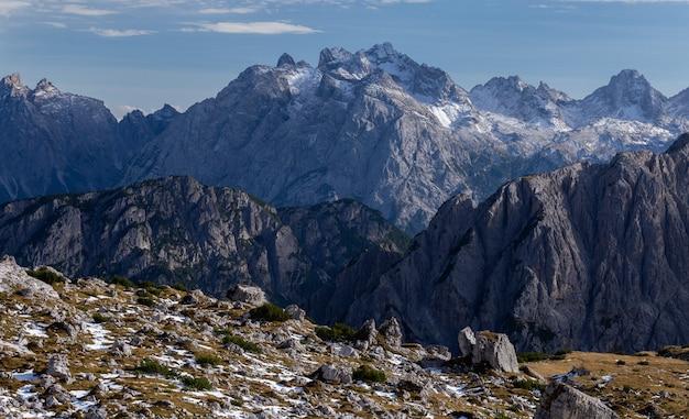 明るい空の下でイタリアアルプスの雪に覆われた岩の息をのむようなショット
