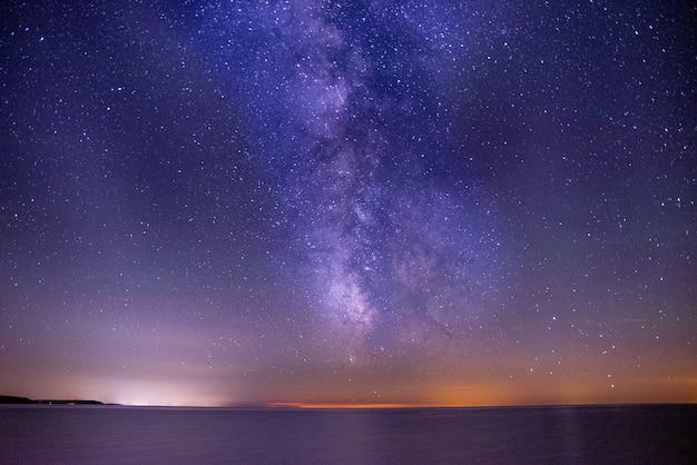 별들로 가득 찬 어둡고 보라색 하늘 아래 바다의 숨막히는 샷