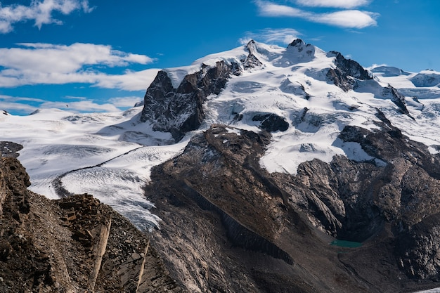Захватывающий снимок заснеженных скалистых гор под голубым небом.
