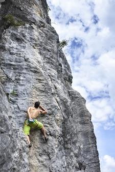 Scatto mozzafiato di un giovane maschio che si arrampica sull'alta roccia a champfromier, francia