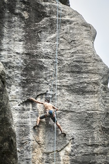 Breathtaking shot of a young male climbing on the high rock in  champfromier, france