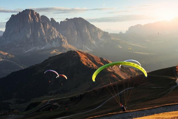 息をのむような光景。夕方の日の出でセチェダドロミテの山々の上空を飛ぶパラグライダーの多く。