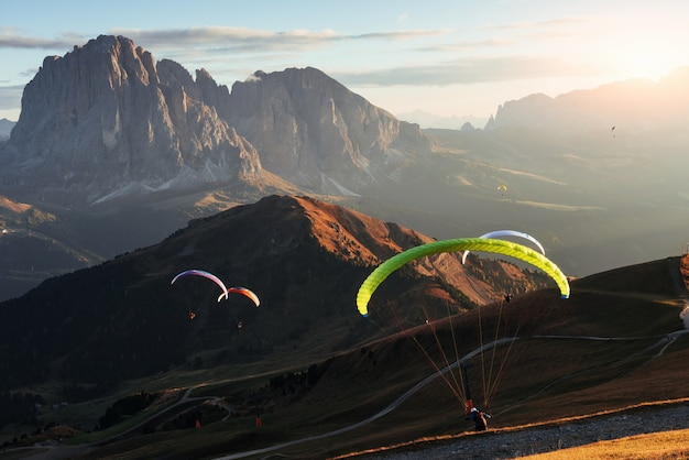 Breathtaking spectacle. many of paragliders flying over the seceda dolomites mountains in the evening sunrise.