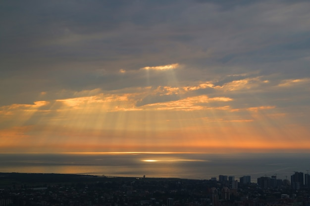 Breathtaking sunrise sky with the angel ladder over the sea and the city