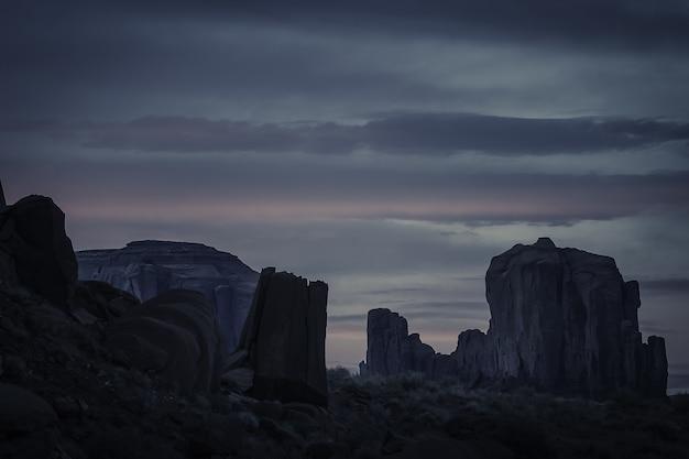 岩の層でいっぱいの峡谷の上の曇り空の息を呑むような夕日