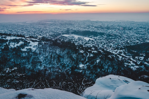 Breathtaking sunset scenery over the city covered with snow in winter