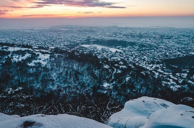 겨울에 눈으로 덮인 도시의 숨막히는 일몰 풍경