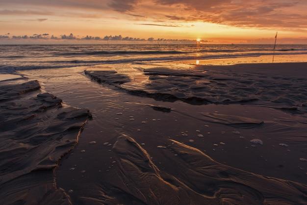 泡立つ海に沈む息を呑むような夕日の風景