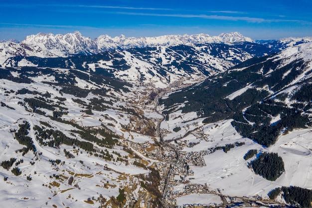 Vista mozzafiato delle montagne boscose coperte di neve durante il giorno