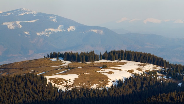 Breathtaking view of magnificent carpathian mountain valley with dry grass and spots of snow on of blurred mighty distant mountain range in early spring.