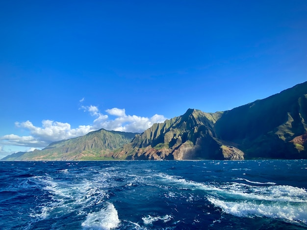 Breathtaking view of the mountain cliffs over the ocean under the beautiful blue sky