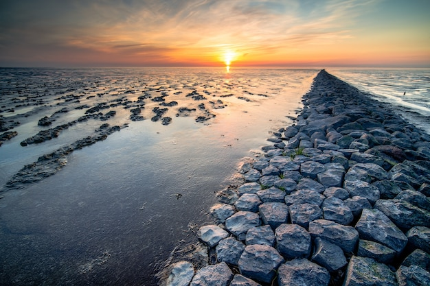 Breathtaking view of mudflat of the waddenzee during low tide under amazing sunset sky with clouds
