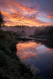 曇り空を貫く夕日の下でキラリと光る森と川の息を呑むような景色