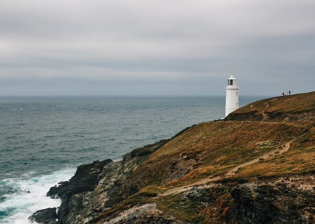 Захватывающий вид на маяк на покрытом травой холме у океана в пасмурный день.
