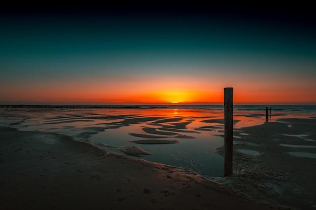 オランダ、ドンブルグの海に沈む夕日の反射の息を呑むような景色