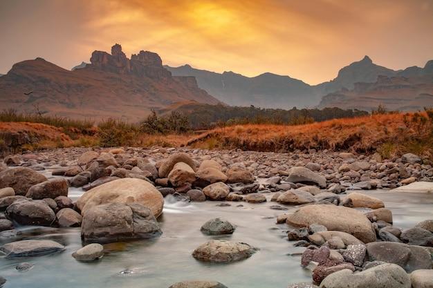 산 너머로 지는 석양과 함께 강가에 있는 바위의 숨막히는 전경