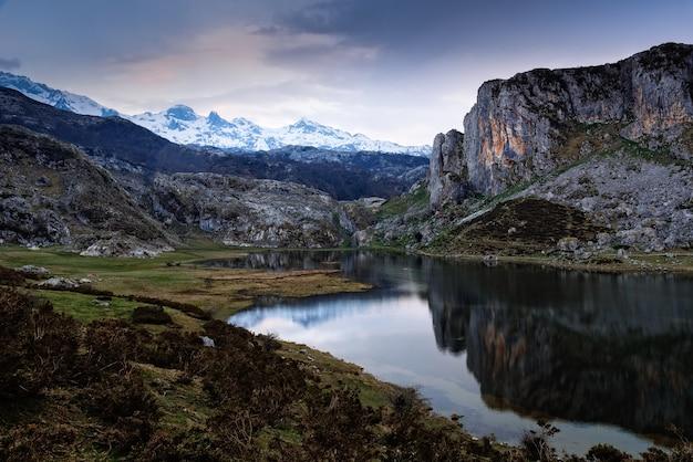 Захватывающий вид на скалистые горы, отражающиеся в воде.