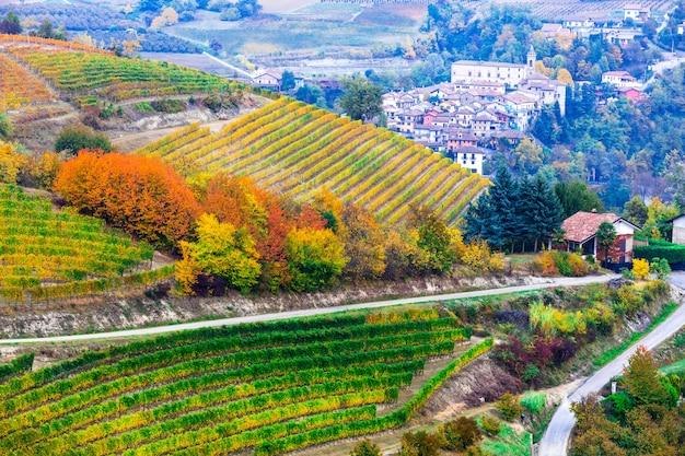 Захватывающий вид на виноградники и деревушки в осенних красках пьемонта. северная италия