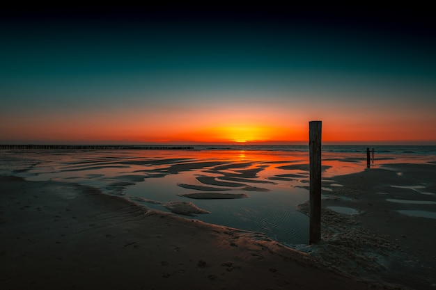 Breathtaking view of the reflection of the sunset in the ocean in domburg, netherlands