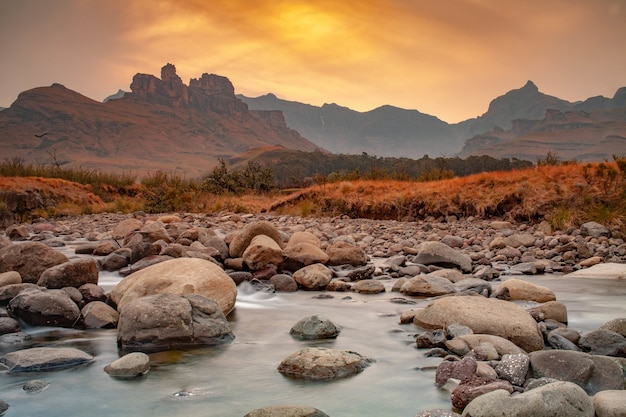Breathtaking view of the rocks on the river with a sunset over the mountains