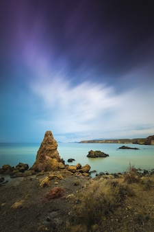 Breathtaking view of the seascape and rocks under a scenic cloudy sky