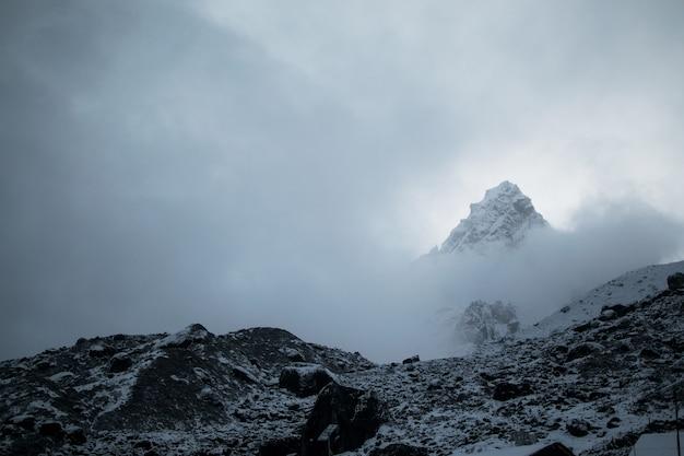 Vista mozzafiato sulla vetta della montagna innevata in un tempo nebbioso