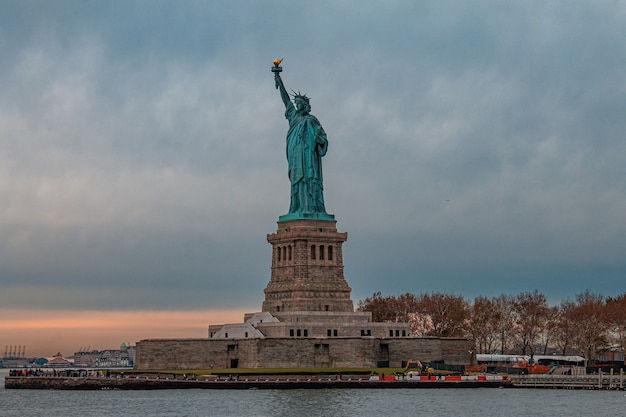 Breathtaking view of the statue of liberty against the dark cloudy sky